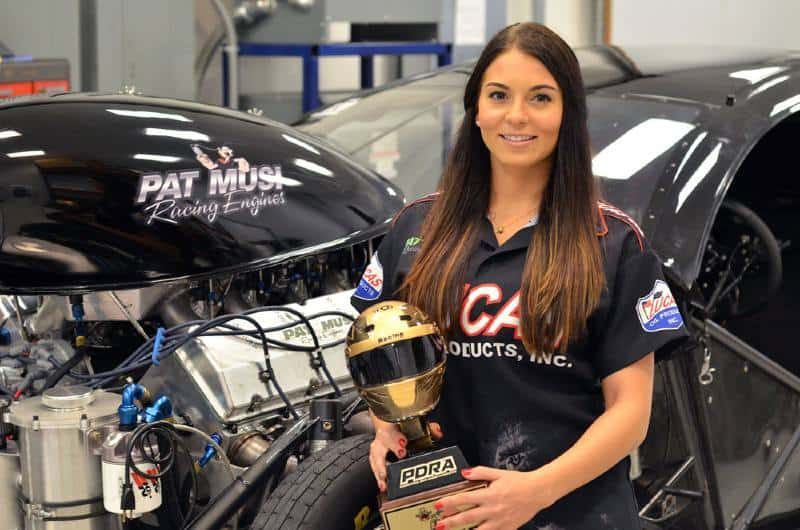 Image of a professional American female drag racer, Lizzy Musi wih trophy